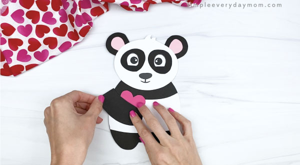 hand gluing arms to panda valentine craft