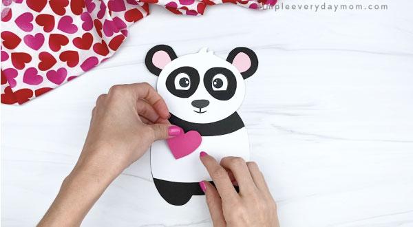hand gluing heart to panda valentine craft