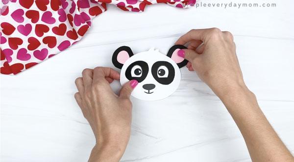 hand gluing ears to panda valentine craft