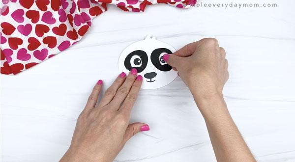 hand gluing eyes to panda valentine craft