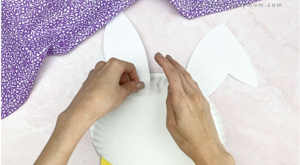 hand taping ears to back of paper plate