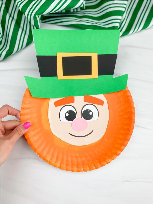 hand holding paper plate leprechaun craft