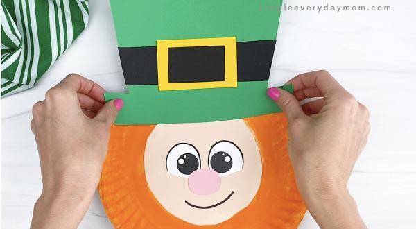 hand gluing hat to paper plate leprechaun craft