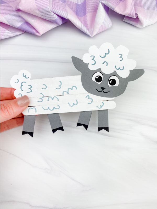 hand holding popsicle stick sheep craft