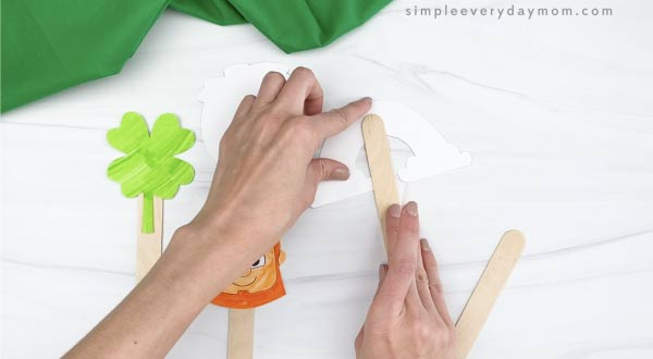 hand taping popsicle stick to back of puppet