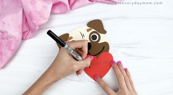 hands writing message on puppy valentine craft