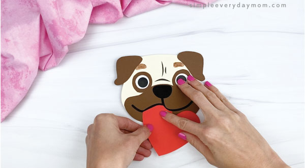hands gluing heart onto puppy valentine craft