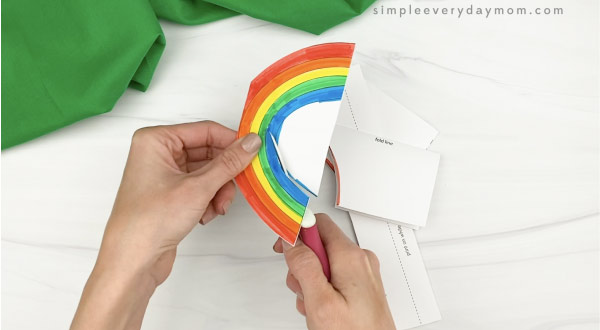 hands cutting out rainbow card craft