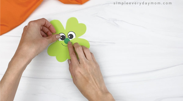 hand gluing nose onto leprechaun shamrock