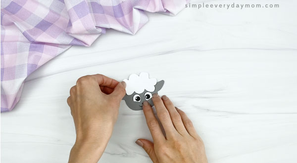 hand gluing head fluff to popsicle stick sheep craft