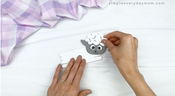 hand gluing head to popsicle stick sheep craft