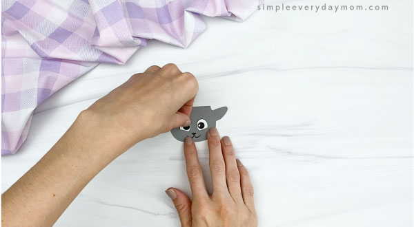 hand gluing eyes to popsicle stick sheep craft
