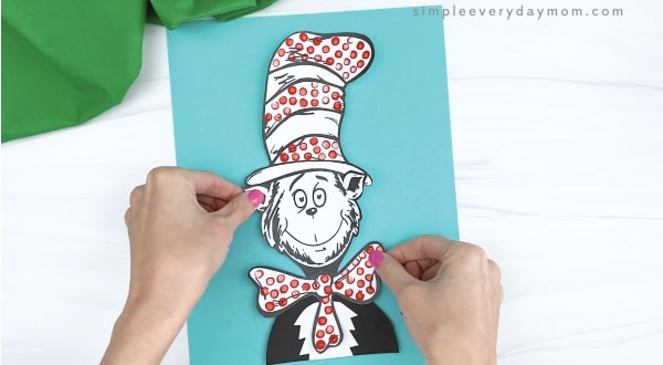hands gluing cat in the hat craft to blue piece of paper