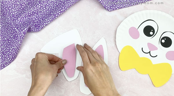 hand gluing inner ears to paper plate Easter bunny craft