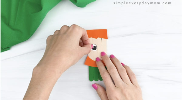 hand gluing eye to popsicle stick leprechaun craft