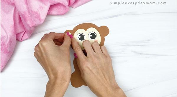 hand gluing inner ear to monkey valentine craft