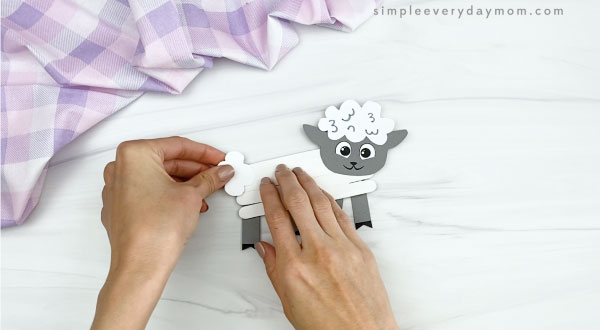 hand gluing tail to popsicle stick sheep craft