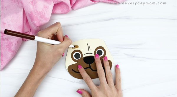 hands drawing eyebrows onto puppy valentine craft