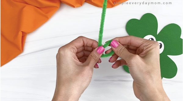 hand twisting green pipe cleaner into foot shape