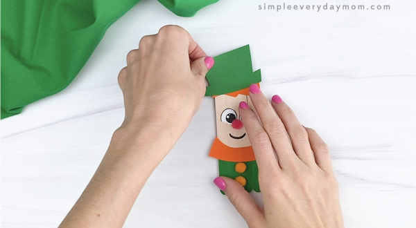hand gluing hat on hand gluing hair to popsicle stick leprechaun craft