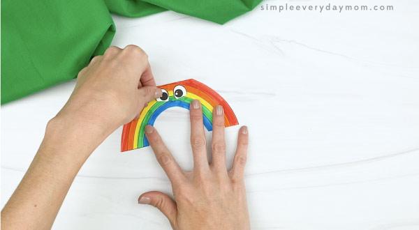 hand gluing eyes to rainbow card craft