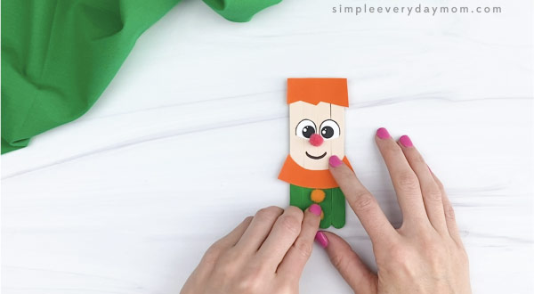 hand gluing pom poms on hand gluing hair to popsicle stick leprechaun craft