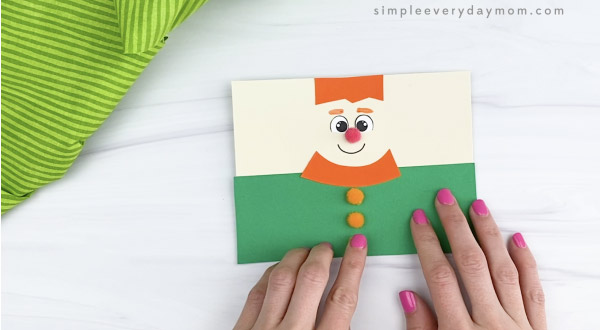 hand gluing pom poms to toilet paper roll leprechaun craft