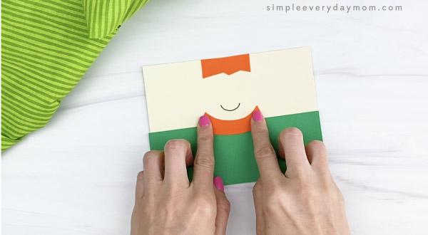 hand gluing beard to toilet paper roll leprechaun craft