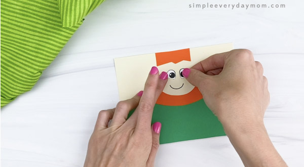 hand gluing eyes to toilet paper roll leprechaun craft