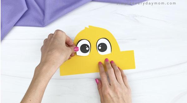 hand gluing eyes to chick headband craft