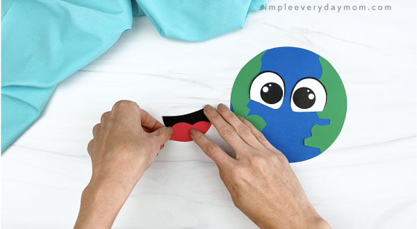 hand gluing tongue to mouth of to paper Earth craft