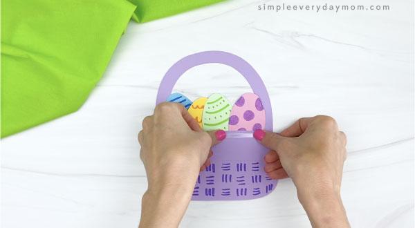 hand stretching glue dot onto Easter basket craft