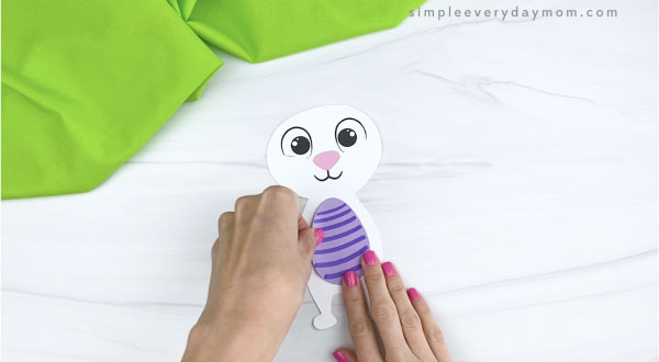 hands gluing egg onto paper Easter bunny craft