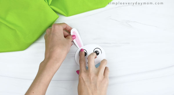 hands gluing ears onto paper Easter bunny craft
