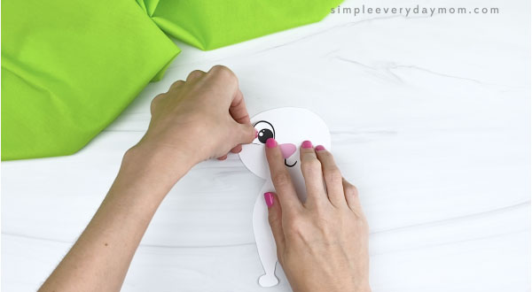 hands gluing eyes onto paper Easter bunny craft