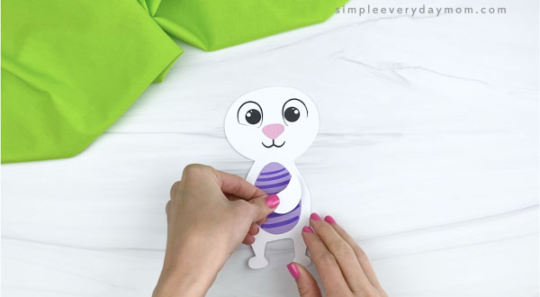 hands gluing arms onto paper Easter bunny craft