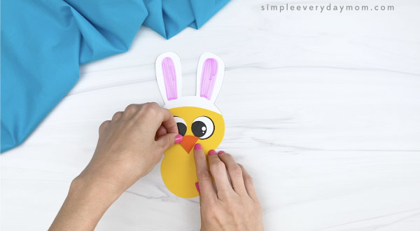 hand gluing eye to Easter chick craft
