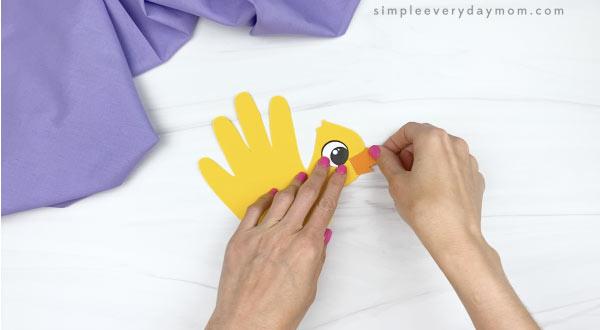 hand gluing beak to handprint chick