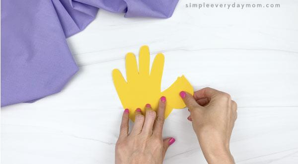 hand gluing head to handprint chick