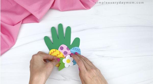 hand gluing flower to handprint Easter card craft