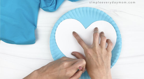 hand tracing heart template on blue paper plate