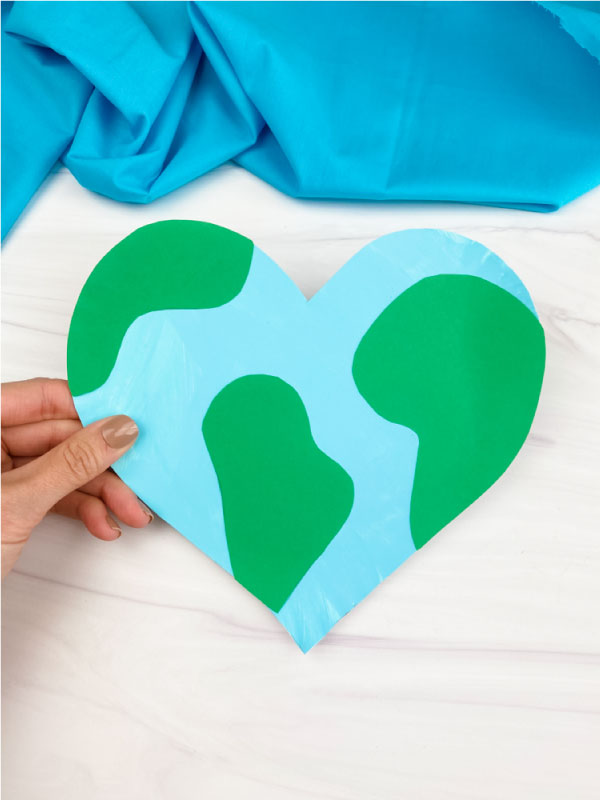 hand holding heart shaped paper plate Earth craft