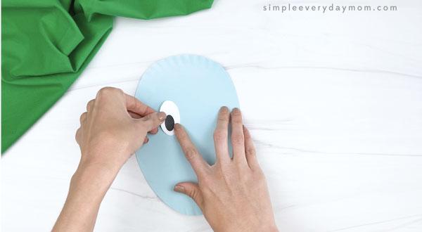 hand gluing eye onto paper plate horton craft