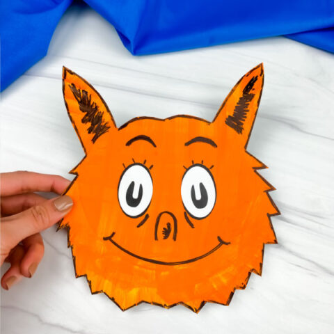 hand holding paper plate fox in socks craft
