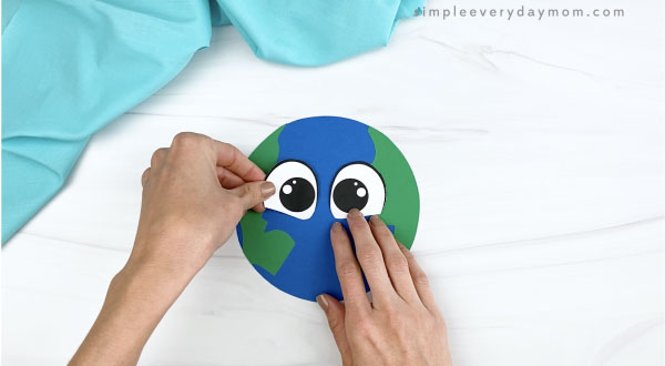hand gluing eyes to paper Earth craft