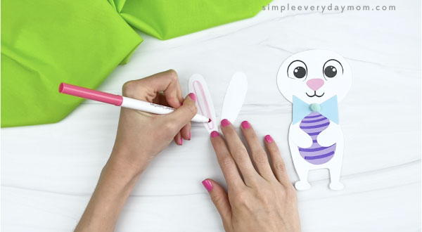 hands drawing inner ears onto paper Easter bunny craft
