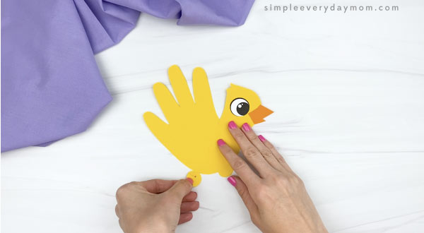 hand gluing top of leg to handprint chick