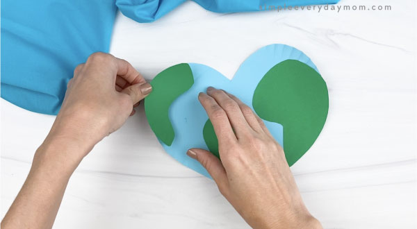 hand gluing land piece on paper plate Earth