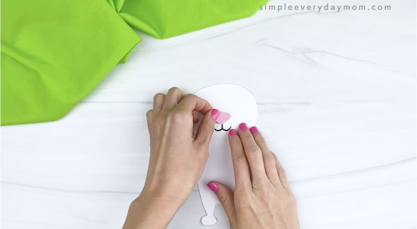 hands gluing nose onto paper Easter bunny craft