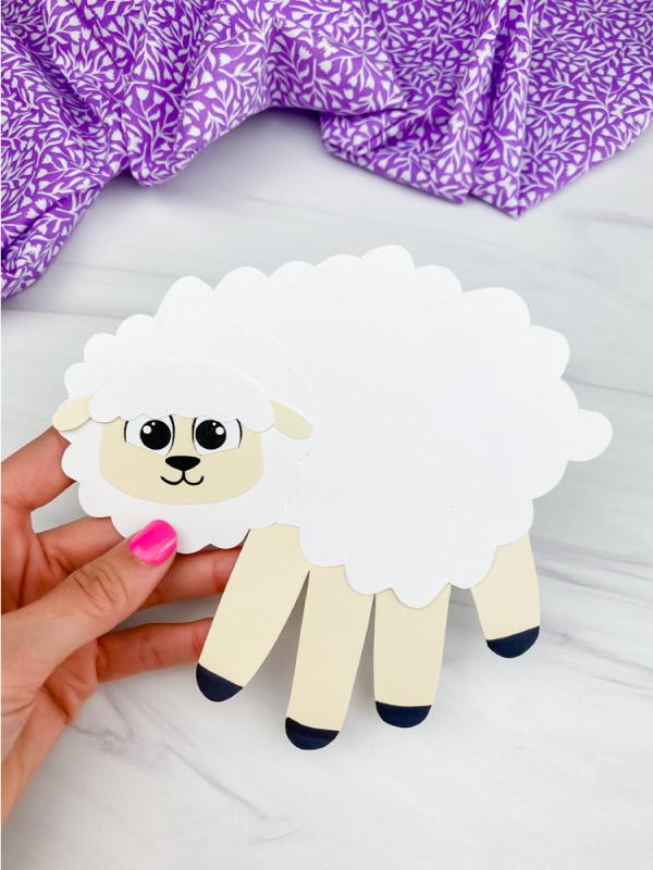 hand holding handprint sheep craft